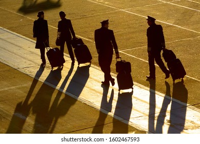 Porto Alegre / Brazil - October 04 2014: Flight attendants and pilots walking with bags. Professionals of aviation including cabin crew and pilot silhouette early in the morning with long shades.