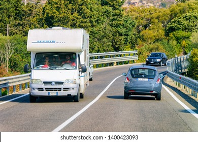 Porto Cervo, Italy - September 9, 2017: Rv cavaran and cars in the road in Costa Smeralda on Sardinia Island in Italy in summer. Motorhome rving on motorway. Camper trailer on highway.