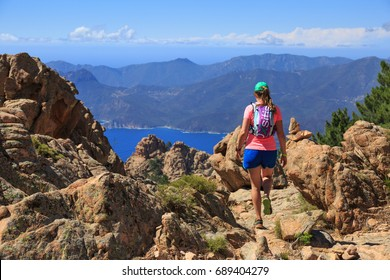 PORTO, CORSICA, FRANCE - july 1, 2017: Woman hiking on a trail in the mountains of Corsica.