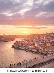 Porto, Portugal. 05 13 2018 old town ribeira aerial promenade view with colorful houses, Douro river and boats at sunset