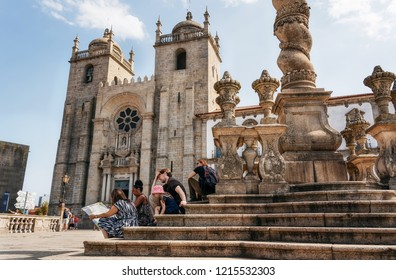 Porto, Portugal - 27 september, 2018: Group of tourists looks at map on stairs of Pillory of Porto against Se cathedral, Portugal