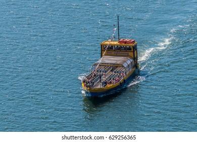 PORTO, PORTUGAL - APRIL 16, 2017: Tourist boat on the River Douro near Ribeira District.