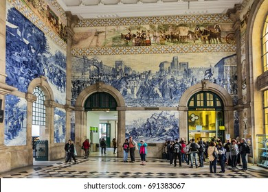PORTO, PORTUGAL - APRIL 16, 2017: Azulejo (earthenware tiles) tile paintings cover vestibule of Sao Bento railway station (1864). Large azulejo representing historical events in Portuguese history.