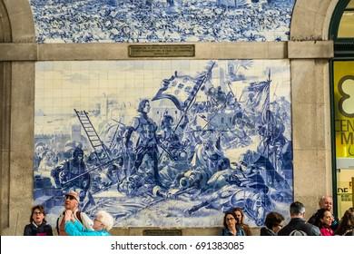 PORTO, PORTUGAL - APRIL 16, 2017: Azulejo (earthenware tiles) tile paintings cover vestibule of Sao Bento railway station (1864). Large azulejo representing historical events in Portuguese history.