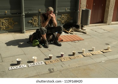 Porto, Portugal - April 22, 2018: Young tramp asking for money in streets of Porto, Portugal during spring 2018. He is very original