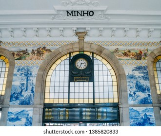 Porto, Portugal - April 29, 2019: Clock of the historical Sao Bento train station in Porto, Portugal. Wall is covered in blue azulejo tiles