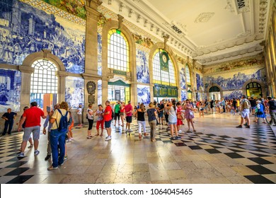 Porto, Portugal - August 13, 2017: tourists visit historic main hall of Sao Bento Railway Station, a train station famous for painted ceramic tileworks on the walls, the blue Azulejos. Unesco Heritage