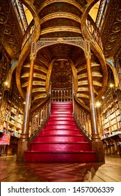 PORTO, PORTUGAL - December 11, 2018: Large wooden staircase with red steps inside library bookstore Livraria Lello in historic center of Porto, famous for Harry Potter film.