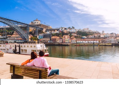 PORTO, PORTUGAL -FEB 24, 2019: Couple seat on bench at Ribeira docks facing Dom Luis I Bridge over Douro River and Gaia town. Porto is the second largest city and famous tourist attraction in Portugal