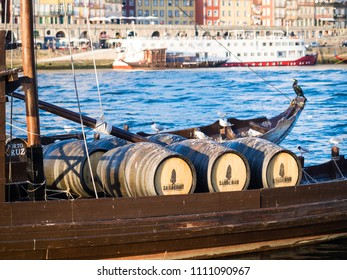 PORTO, PORTUGAL - FEBRUARY 18, 2018: Barrels with port wine on the Rabelo boats on the Douro river in the Old Town of Porto, Portugal.