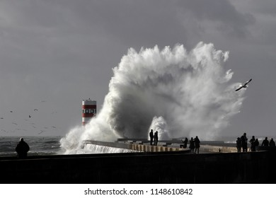 Porto, Portugal - January 2, 2016: People watching the big stormy sea waves on a pier from the north of Portugal