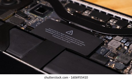 Porto, Portugal - January 5 2020: Warning label on Macbook Pro motherboard - close up diagonal shot