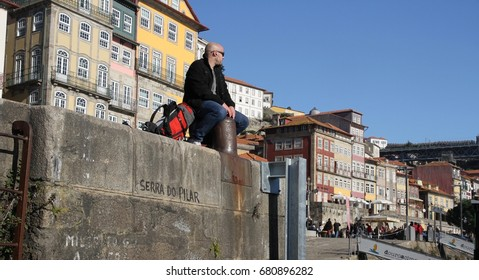 PORTO, PORTUGAL - JANUARY 8:  A man sitting on the concrete river wall watching the boats on the Douro River in Porto, Portugal on the 8th January, 2017.