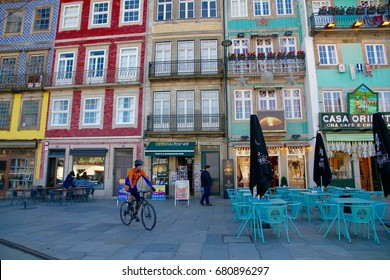 PORTO, PORTUGAL - JANUARY 8: An unknown person riding a bicycle in front of colorful buildings in the city of Porto Portugal on the 8th January, 2017.