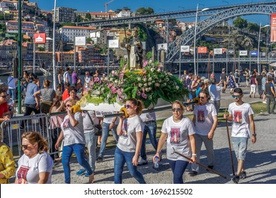 Porto, Portugal - July 22 2018: Catholic Christian religious holiday procession. Flower decorated statues carried by people on the bank of Douro river at Vila Nova de Gaia, with Luis I Bridge visible.