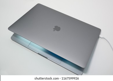 """Porto, Portugal - July 8th 2018: MacBook Pro 15"""" laptop / notebook computer with lid partially closed and USB-C cable connected"""