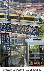 Porto, Portugal - June 14 2018 : View from the top of the Funicular dos Guindais of the funicular ascending as a train travels over the Ponte de Dom Luis I bridge in Ribeira, Porto, Portugal