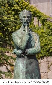 "Porto, Portugal - June 14 2018 : Statue of journalist and novelist, Arnaldo Gama, 1828 - 1868, sculptured by Rogerio Azevedo in 1971, in front of the Fernandinas Walls or'Muralhas Fernandinas"", Porto"