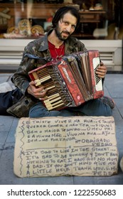 Porto, Portugal - June 14 2018 : Sad looking poor man with a beard and a sign kneeling on the pavement, asking for help on the streets of Porto, by busking and playing a tatty, broken, old accordion