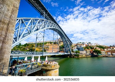 PORTO, PORTUGAL - JUNE, 14: Tourists relax at the restaurant under famous landmark Luis bridge at day time on June 14, 2015 in Porto, Portugal