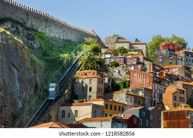 Porto, Portugal - June 15 2018 : View of the Funicular dos Guindais railway ascending the hill past the houses, and running from the riverfront to the Praca da Batalha, in Porto, Portugal