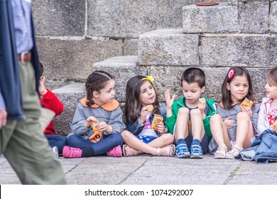 PORTO, PORTUGAL - June 2, 2017: A group of young kids having their snacks on the ground during their excursion.