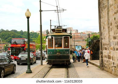 PORTO, PORTUGAL - JUNE 21, 2018: tourists climbing on vintage tram in the old european city of Porto, Portugal