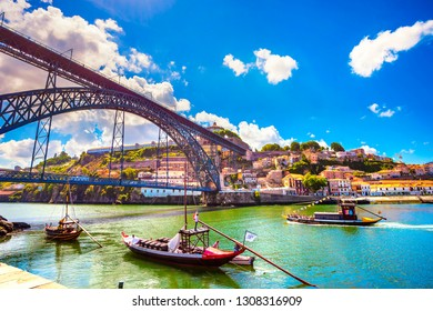 PORTO / PORTUGAL - JUNE 26, 2009: Traditional boats in Douro river and Dom Luis iron bridge. On the other side Vila Nova de Gaia and Port Wine cellars tourist attraction.