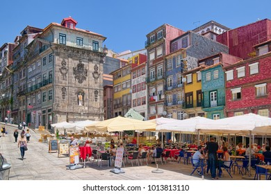 PORTO, PORTUGAL - JUNE 5, 2015: Colorful houses and outdoor cafes at historic Ribeira Square of Porto, a popular place for tourists and locals.