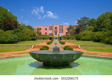 PORTO, PORTUGAL - JUNE 7, 2015: Fountain on wide alley in front of pink building of Serralves Villa (Portuguese: Casa de Serralves) in Serralves Park of Porto, Portugal.