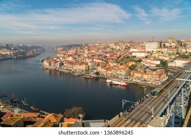 PORTO, PORTUGAL - MARCH 1, 2019: Tram cars and people passing over Dom Luis I Bridge with a scenic view on the historic center of Porto, Portugal on March 1st, 2019.