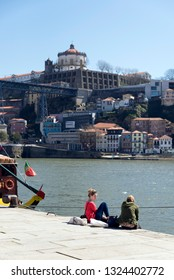PORTO, PORTUGAL - MARCH 11, 2014: Two young women sitting at the edge of the River Douro