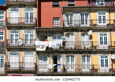 PORTO, PORTUGAL - MARCH 11, 2014: Woman at the window of his house in the historic center of Porto, Portugal