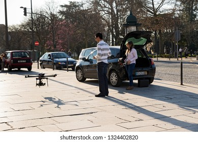 PORTO, PORTUGAL - MARCH 11, 2014: Young technicians using laptop by UAV drone in street