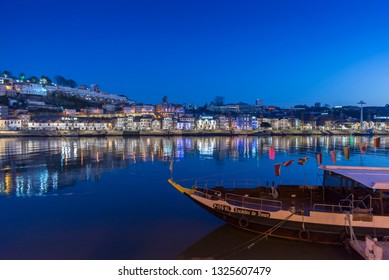 PORTO, PORTUGAL - MARCH 11, 2014: Colorful view of sunset along the riverfront with lights reflecting in the Douro River in Porto, Portugal