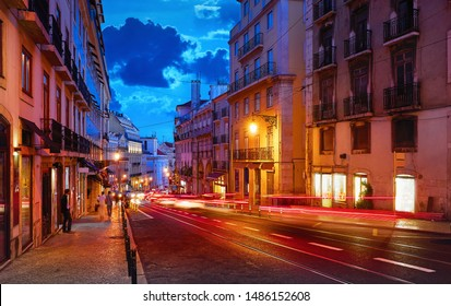 Porto, Portugal. Nighttime city life. Old town street with evening illumination and sky with clouds blue hour. Car speed lights on the road with asphalt.