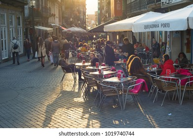 PORTO, PORTUGAL - NOVEMBER 16, 2017: People at a street restaurant at Old Town of Porto. Porto is a second largest city and popular tourist destination in Portugal