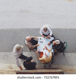 PORTO, PORTUGAL - OCTOBER 04, 2014: A group of elderly people play cards gathered around a table set on the street.