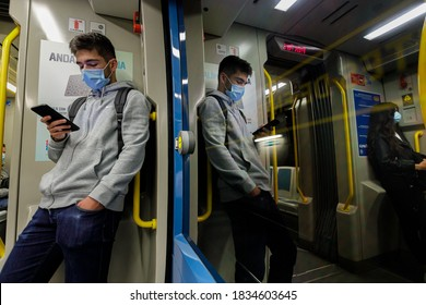 Porto, Portugal - October 15, 2020: Young man wearing a face mask traveling on the Porto subway metro looking at his smartphone during the covid-19 pandemic