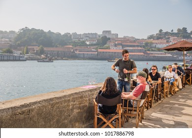 PORTO, PORTUGAL - OCTOBER, 2016: cityscape. view of open-air street cafe on the banks of the River Douro in Porto Portugal