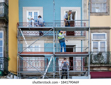 Porto, Portugal - October 26, 2020: Construction workers building a safety scaffold frame structure around and an old colorful building facade with bright blue tiles.