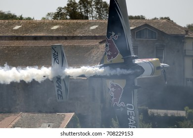 Porto, Portugal - September 1, 2017: Red Bull air race. Training day. Airplane in a tight and beautiful maneuver on the bank of the Douro river of Vila Nova de Gaia, in the middle of smoke.