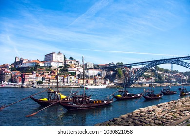 PORTO, PORTUGAL - SEPTEMBER, 2016; Downtown cityscape by Douro river with wine barrels on old boats, Porto, Portugal