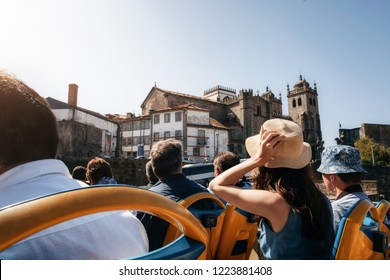 Porto, Portugal. Tourists on open top sightseeing bus Hop on hop off in explore city. Cathedral Seu on the background