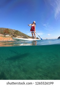 Porto Rafti, Attica / Greece - December 22 2018: Underwater photo of attractive unidentified fit female dressed as Santa Claus practising SUP or Stand Up Paddle board at Christmas time
