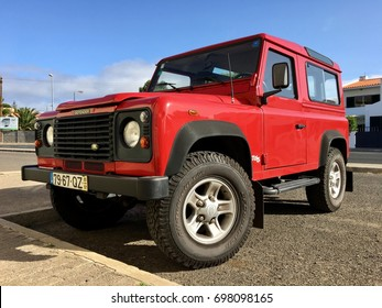 Porto Santo, Portugal - August 17, 2017: Red Land Rover Defender Td5 is a British four-wheel-drive off-road SUV developed from the original Land Rover Series stands parked