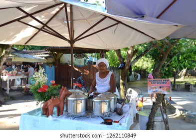 Porto Seguro/Bahia/Brazil - January 01, 2018: Acarajé seller in the historical center of Porto Seguro. Baiana selling typical food of the region. Old lady selling food. Street market at Bahia.