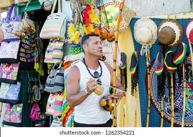 Porto Seguro/Bahia/Brazil - January 01, 2018: Man playing typical brazilian instrument called berimbau, in front of shops in the historic center of Porto Seguro.