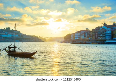 Porto skyline at sunset, wine boat in the foreground. Portugal
