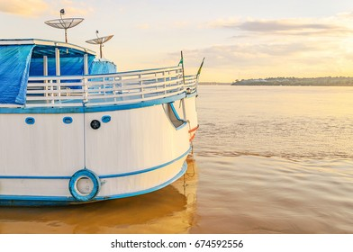 PORTO VELHO, BRAZIL - JUNE 17, 2017: Stern of boats on banks of the Rio Madeira river at sunset. Boats departs from Estrada de Ferro Madeira-Mamore carrying tourists with some onboard services.